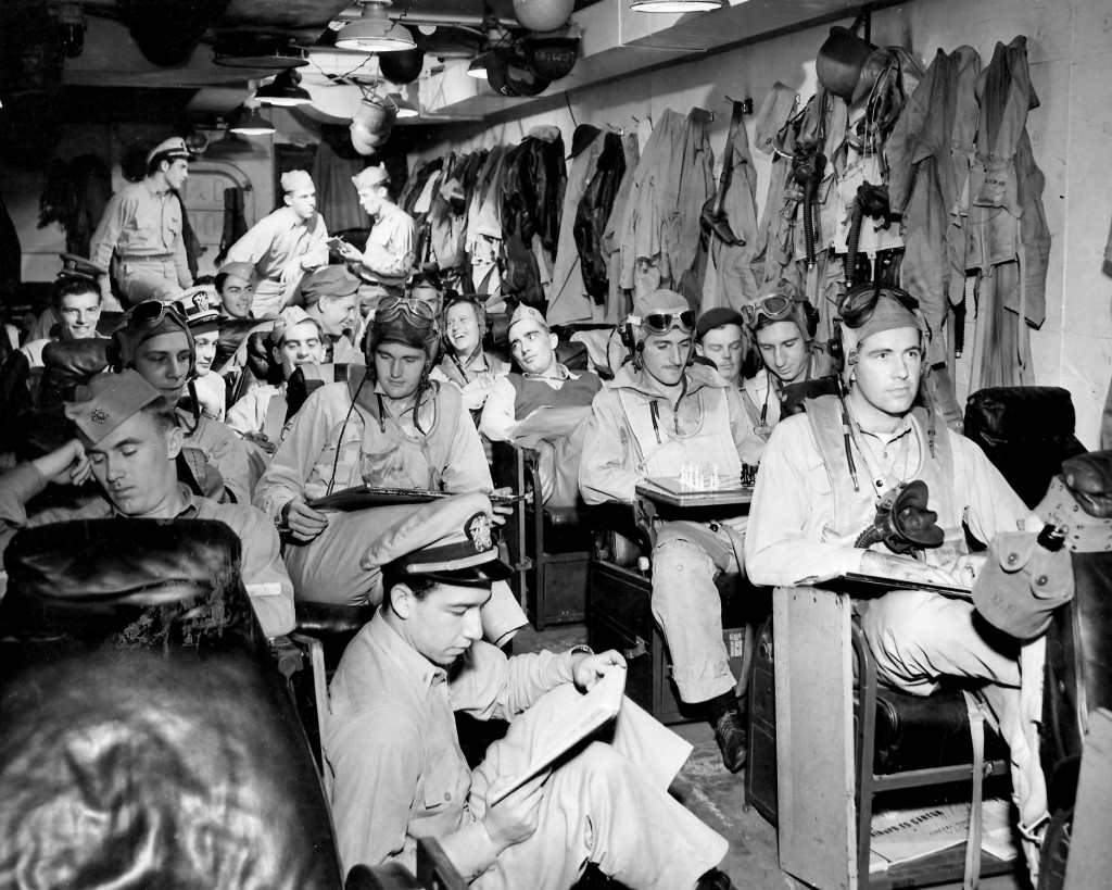Airmen are prepared men---In a photograph notable for its sharpness and depth of perspective, Navy fighter pilots are snapped in the ready room of their aircraft carrier before a strike somewhere in the Pacific in a recent battle operation   Feb. 27, 1945