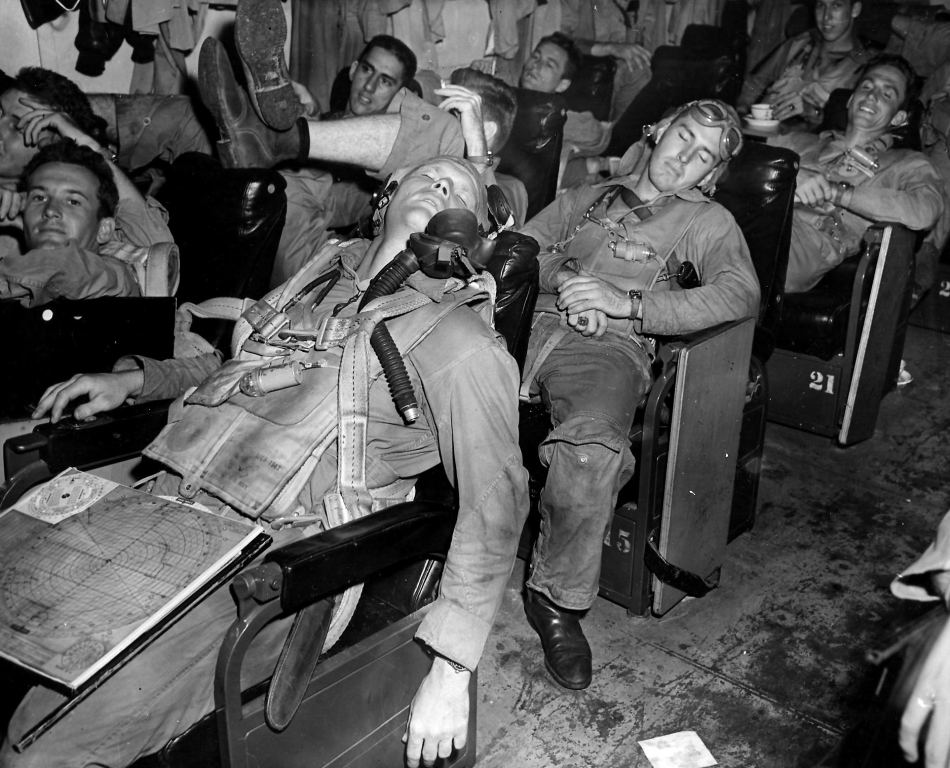Airmen's Restful Air -- Indicative of their lack of tension, Navy fliers Lieutenant (jg) John H. Cantrell (left) and Lieutenant John L. Carter catch 40 winks in the ready room of their carrier while awaiting the word to man their planes during a recent battle action in the Pacific.  Lt(jg) Cantrell is from Portales, N.H. and Lt. Carter from Jacksonville, Florida.  Released November 28, 1944.
